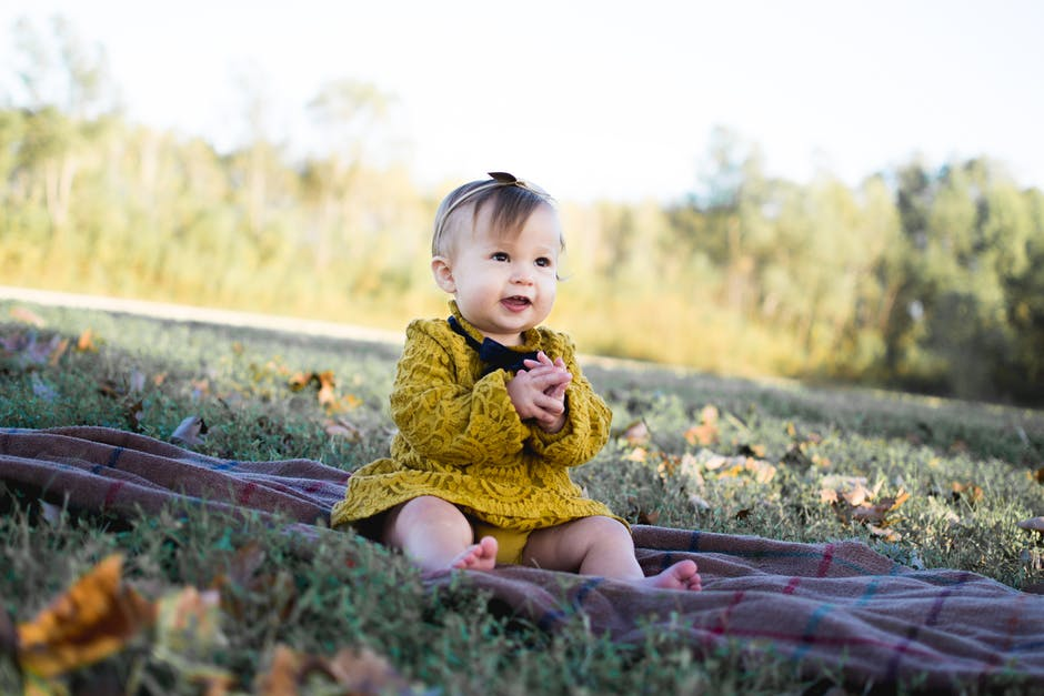 A small child is sitting in the grass